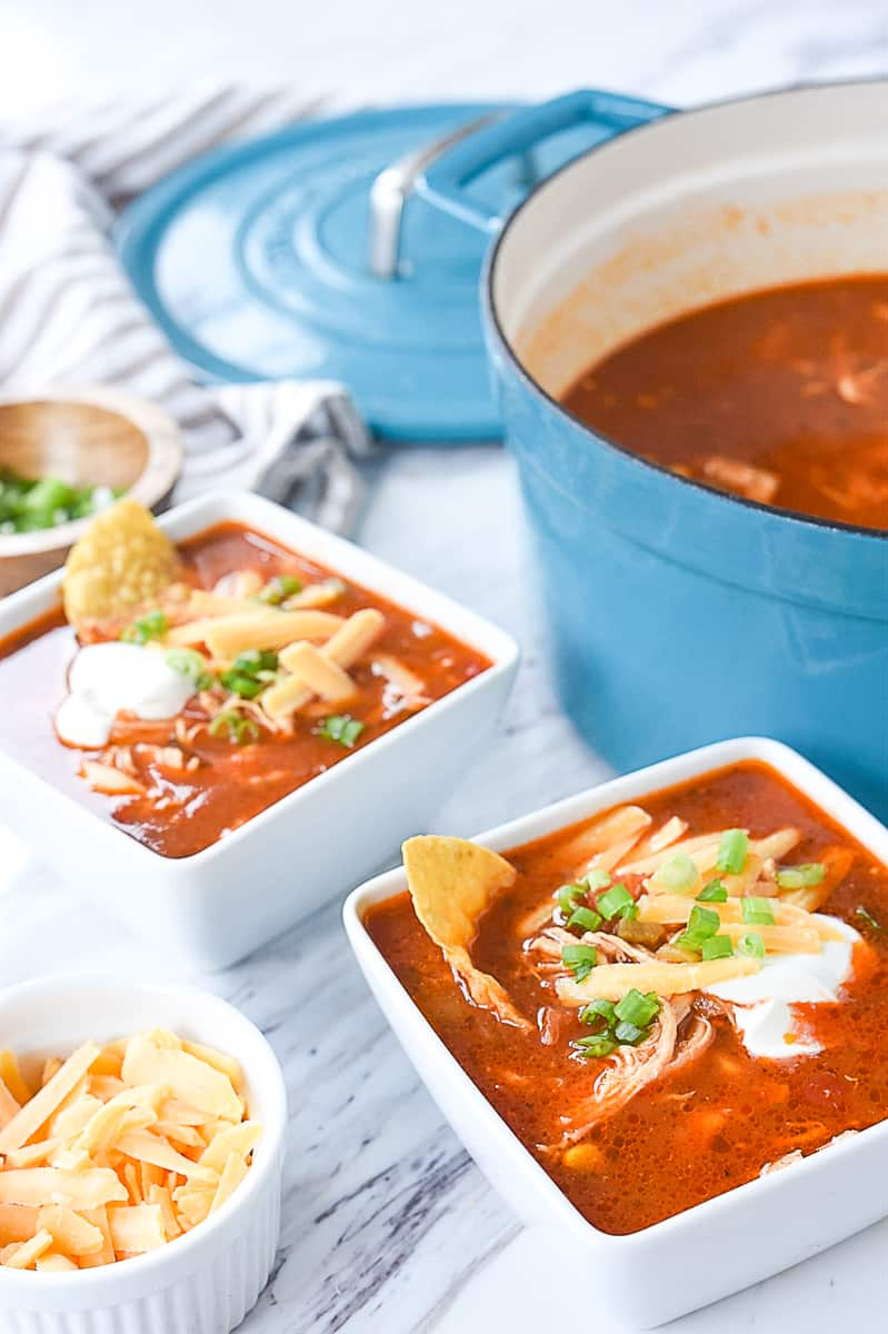 two bowls of soup with cheese on top