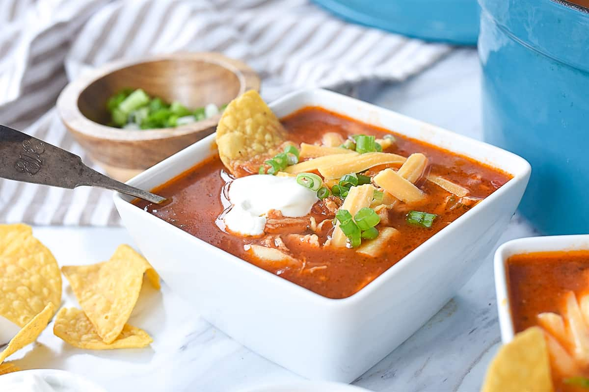 chicken enchilada soup with sour cream on top