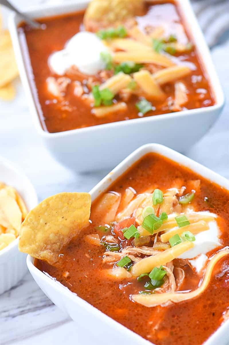 two bowls of enchilada soup with cheese on top