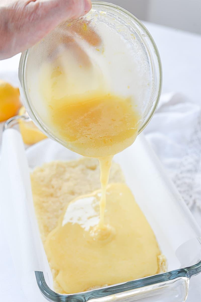 pouring filling over lemon bars