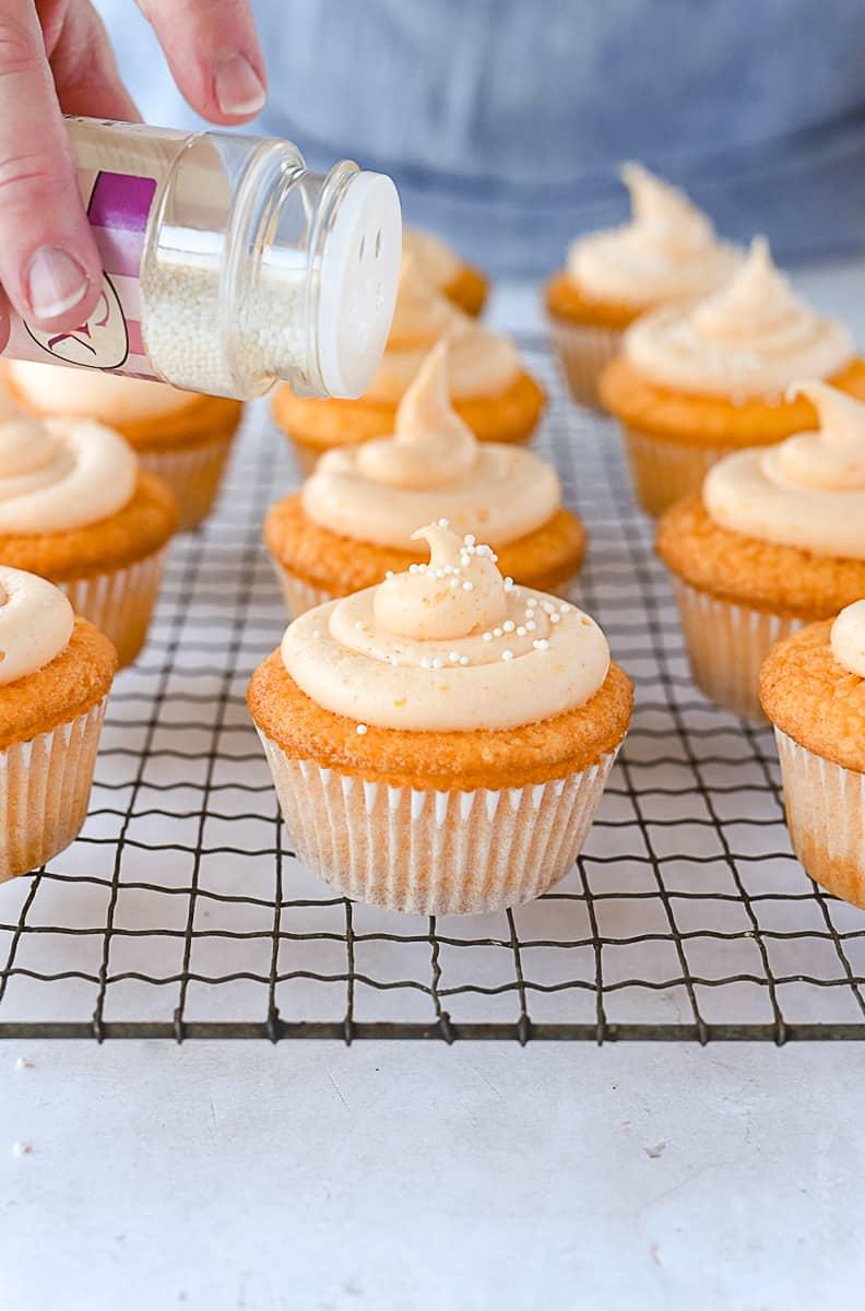 adding sprinkles to orange cupcakes