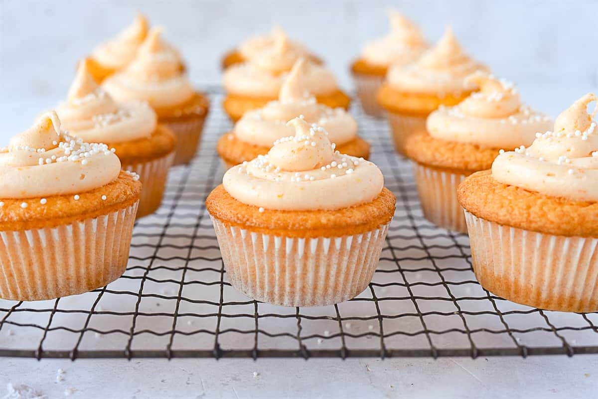 rows of orange cupcakes on a rack