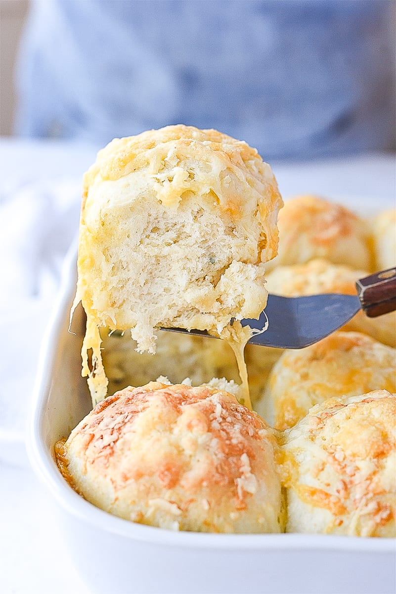 lifting a cheese herb roll out of the pan