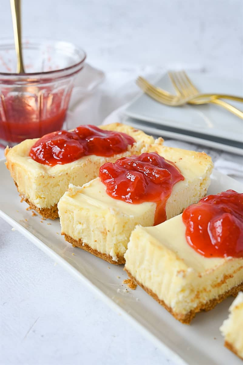slices of cheesecake with strawberry sauce
