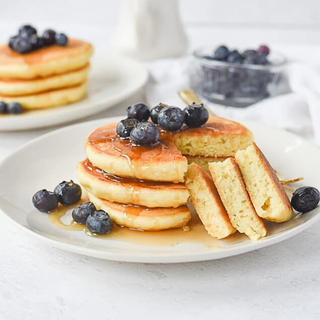 plate of 3 pancakes with blueberries