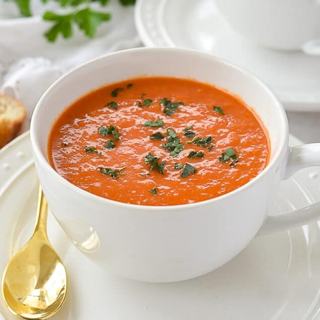 bowl of roasted red pepper soup with parsley on top
