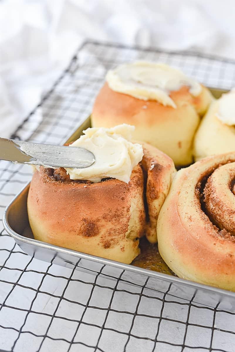 frosting a cinnamon roll