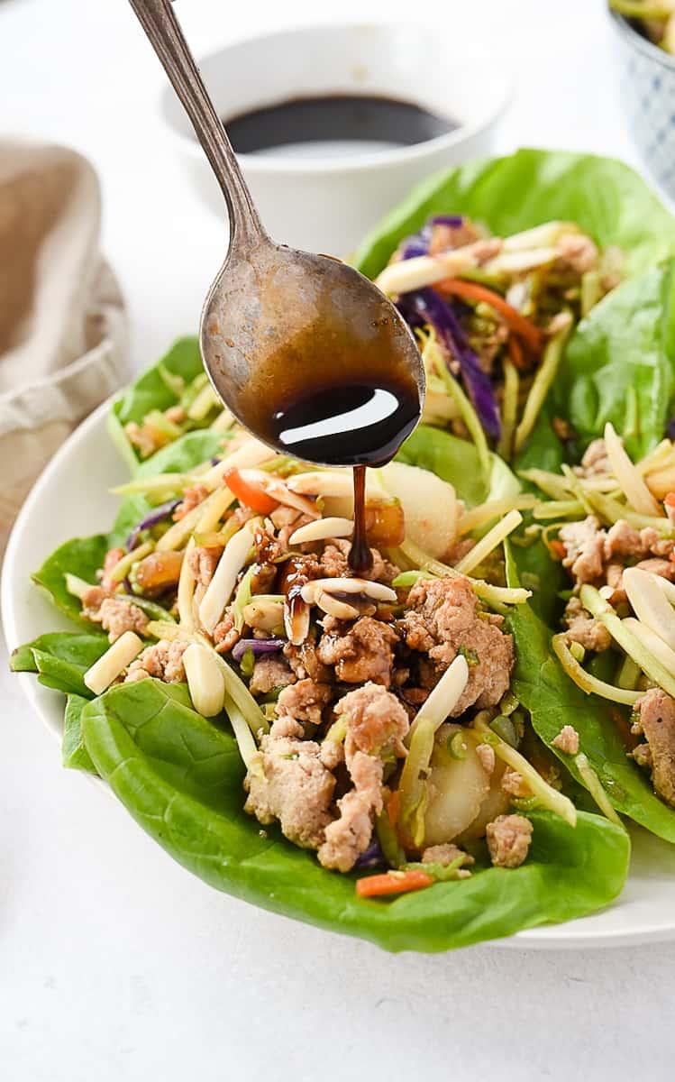 drizzling teriyaki sauce on lettuce wraps