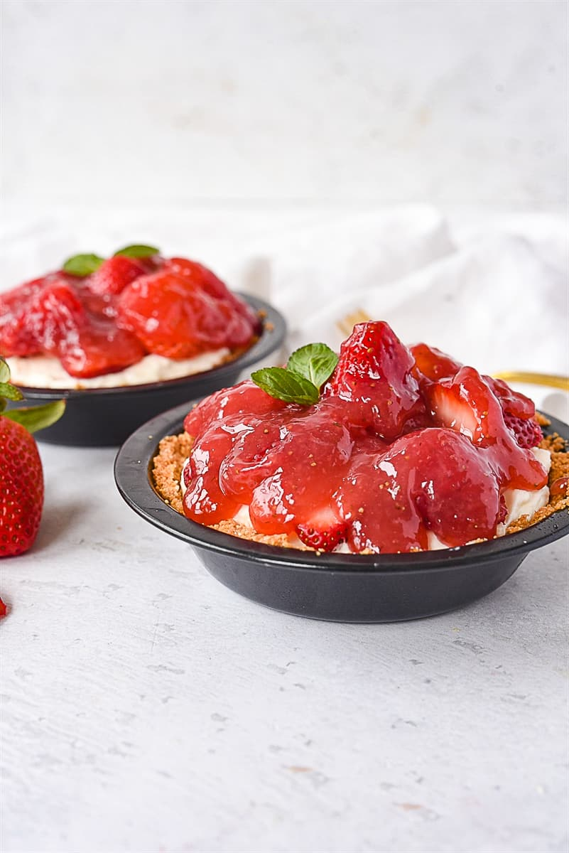 two mini strawberry pies in graham cracker crust