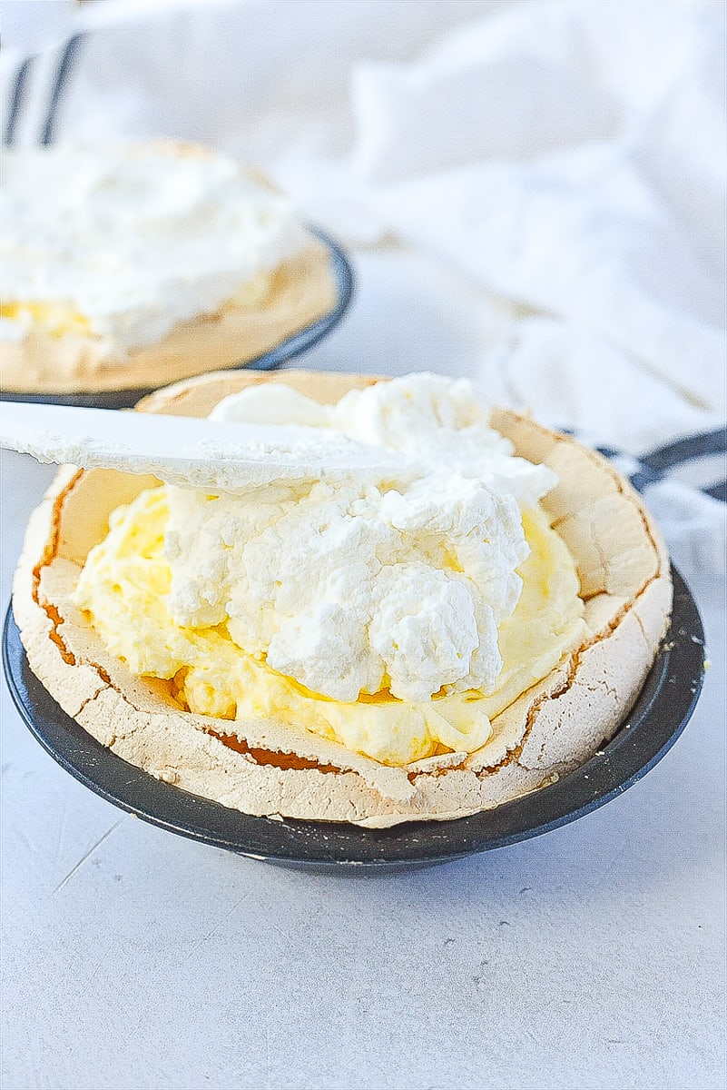 topping lemon angel pie with whipped cream.