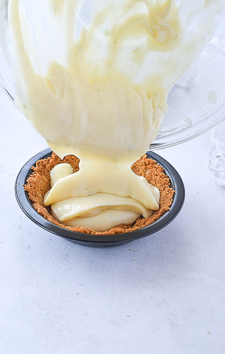 pouring key lime pie filling into crust