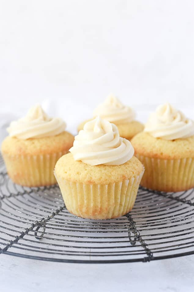 four cupcakes with frosting