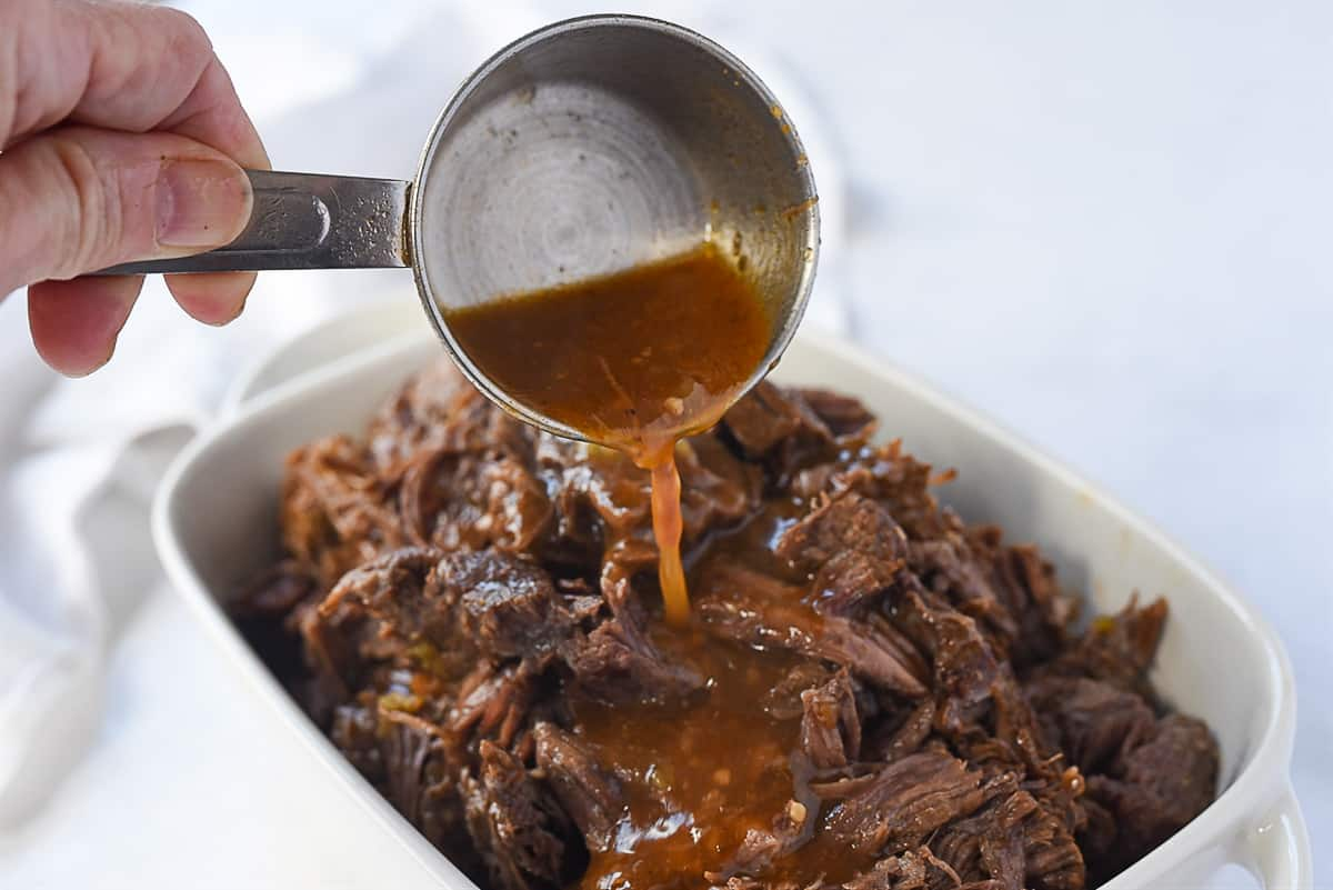 pouring gravy over beef barbacoa