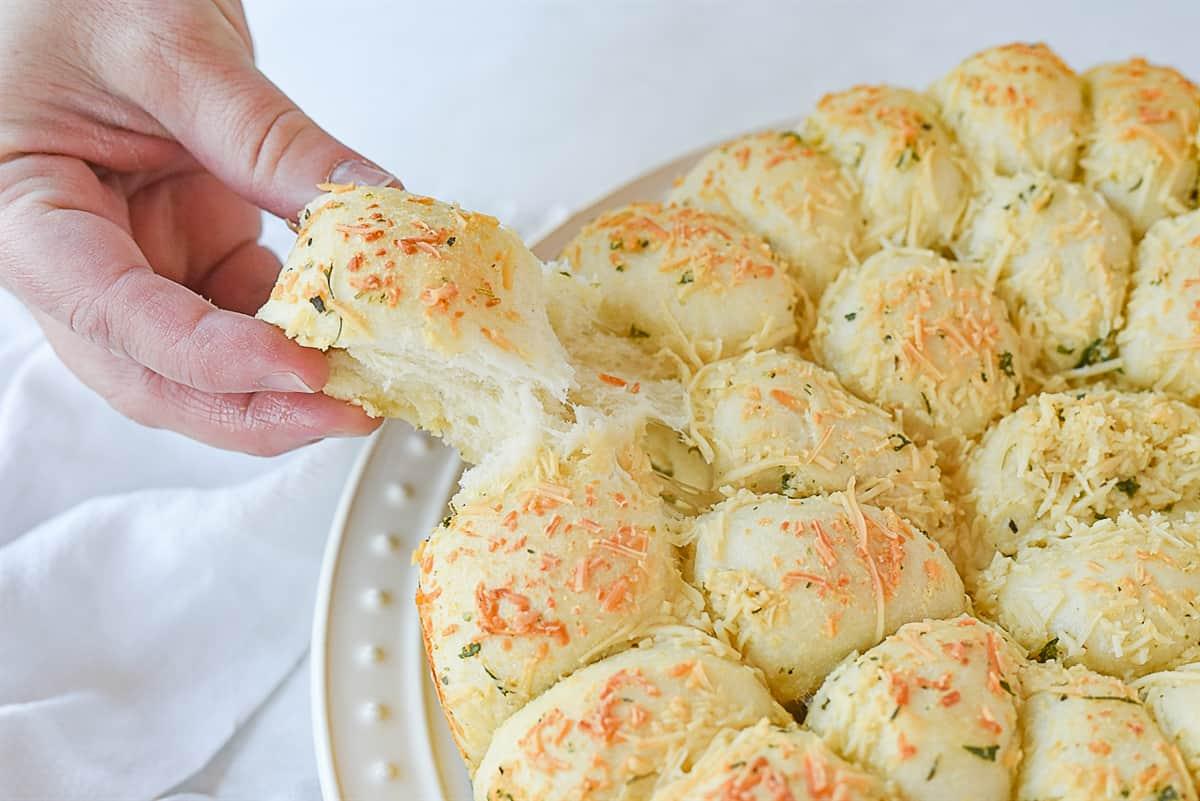 hand pulling a piece of cheesy garlic bread