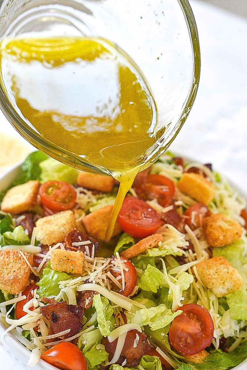 pouring dressing over house salad