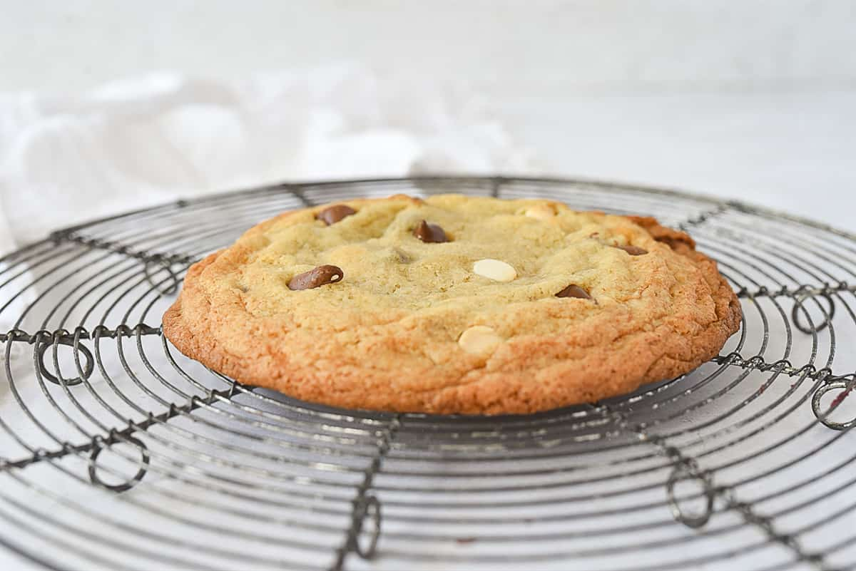 one chocolate chip cookie on a cooling rack