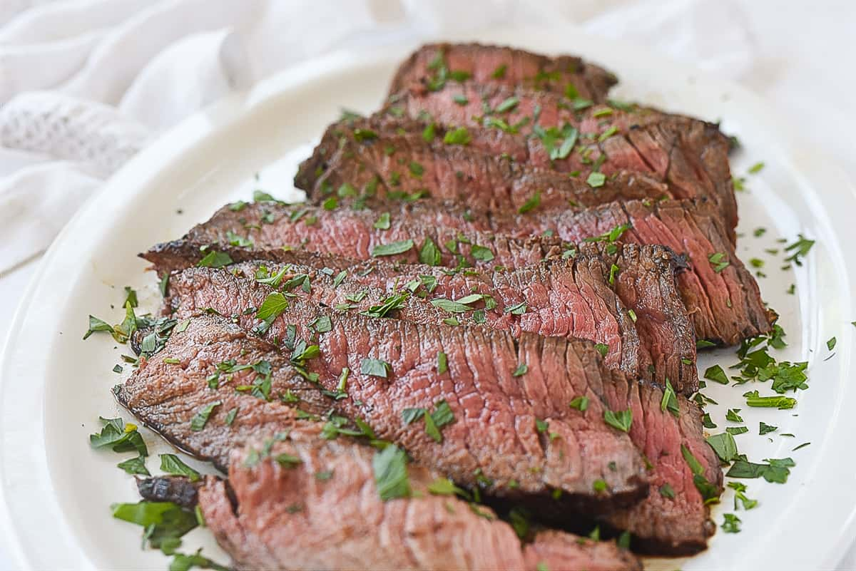 sliced london broil on a white plate