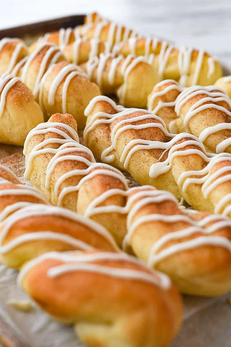 drizzled cinnamon breadsticks on baking sheet