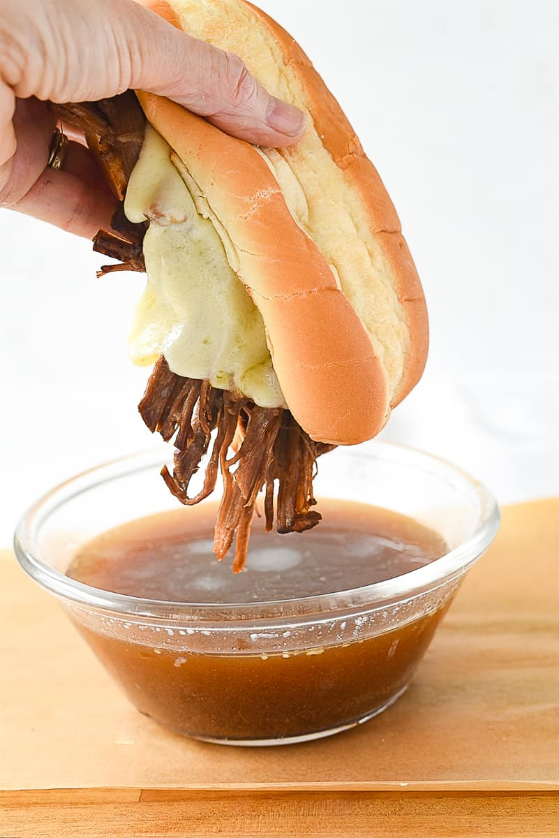 dipping tri tip sandwich in au jus