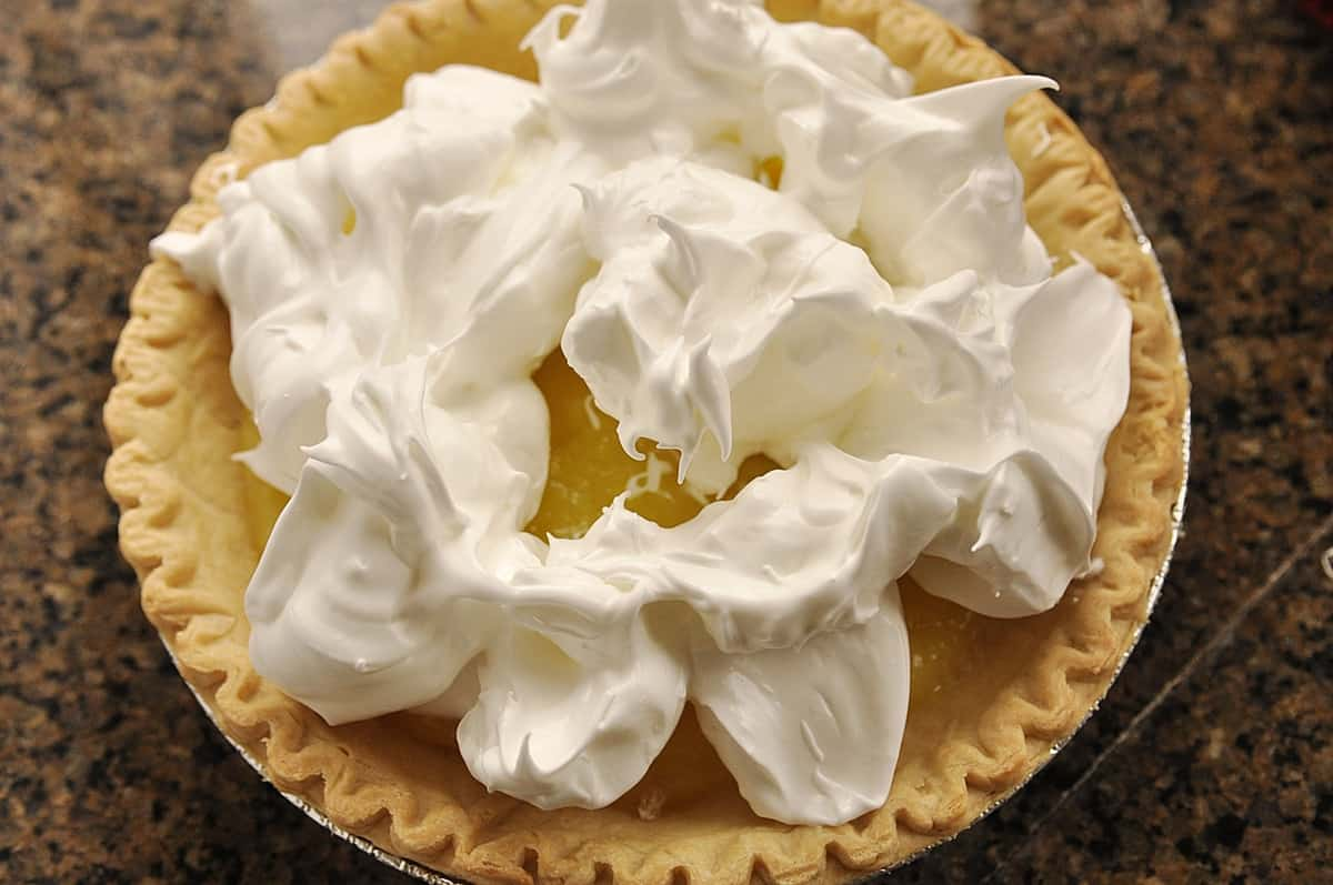 spooning meringue on a lemon pie