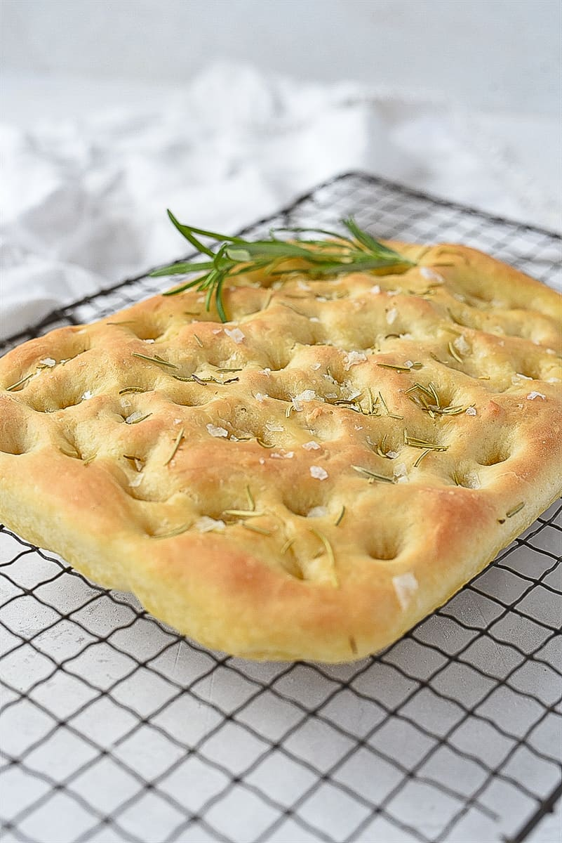 loaf of focaccia bread on a cooling rack