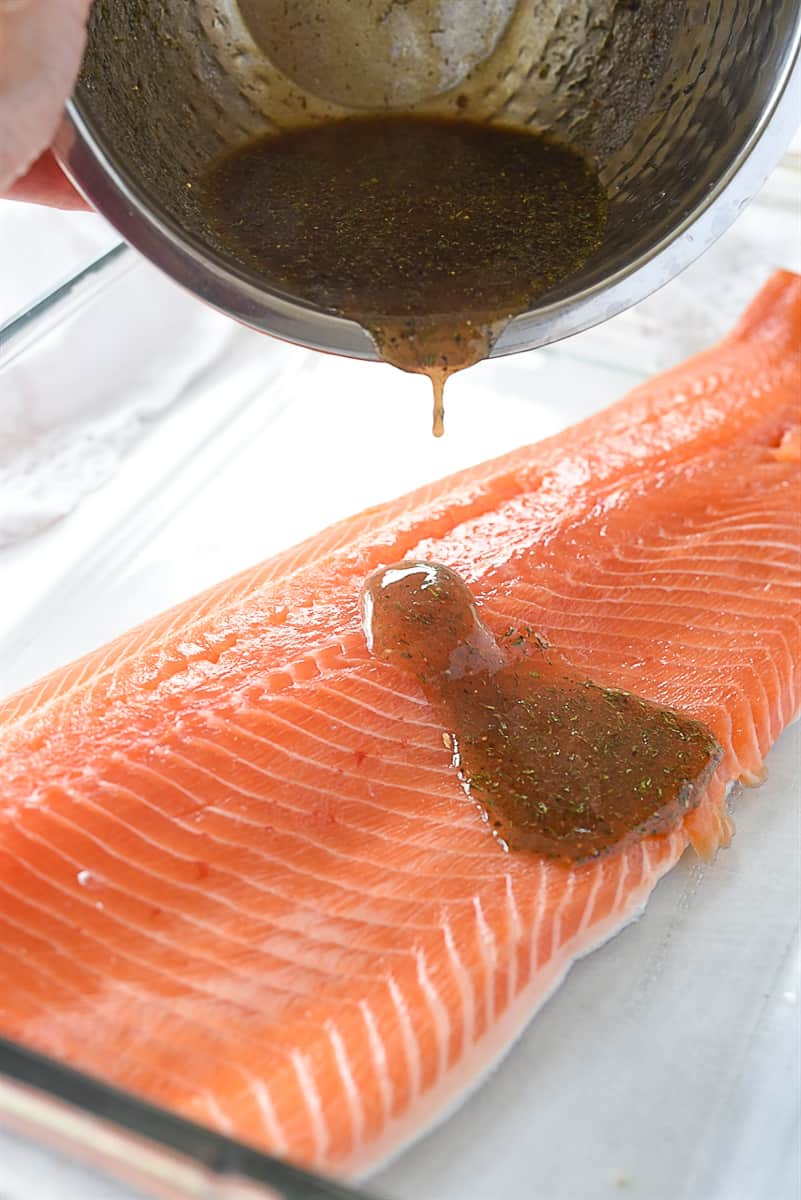 pouring marinade over salmon