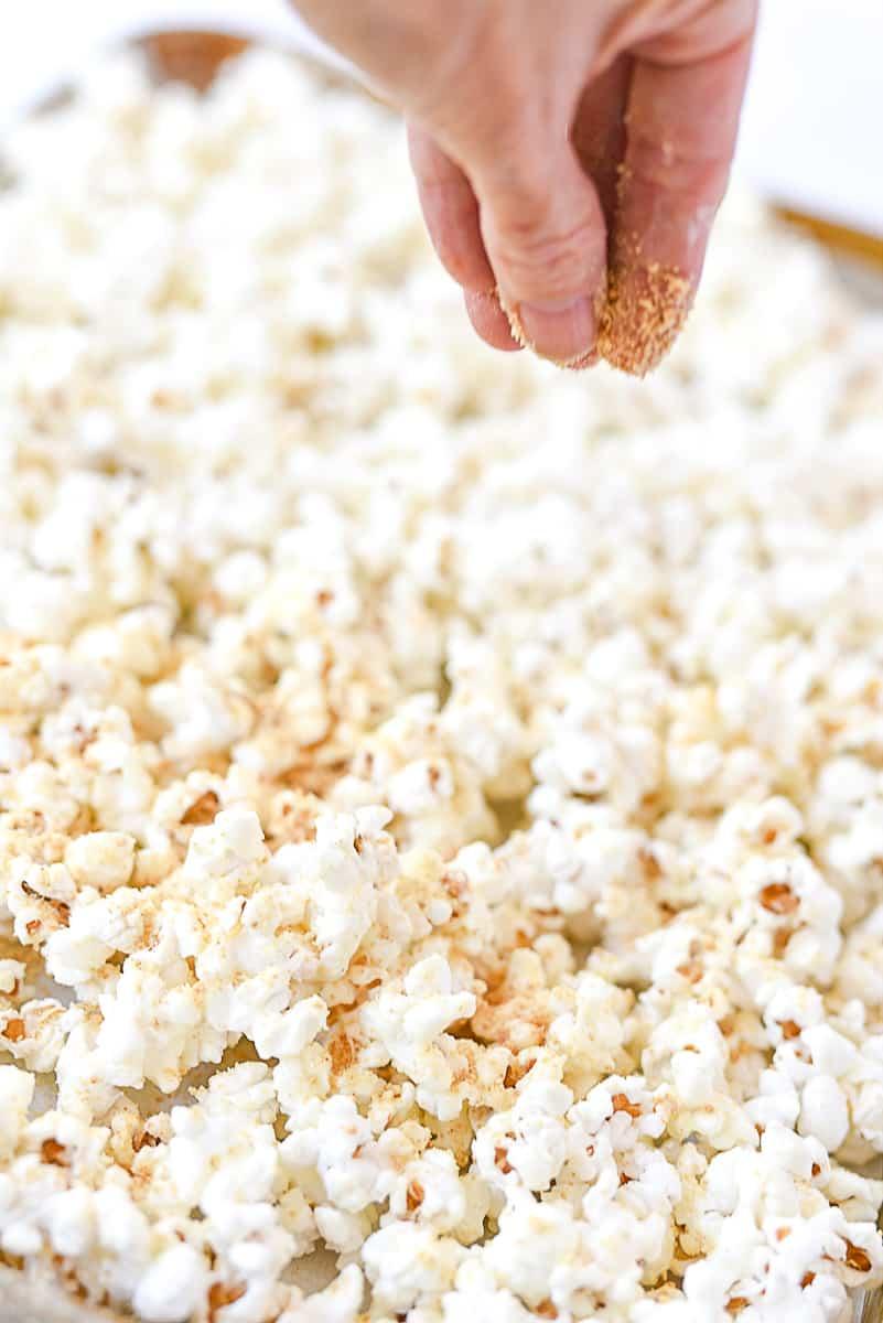 sprinkling graham crackers on popcorn