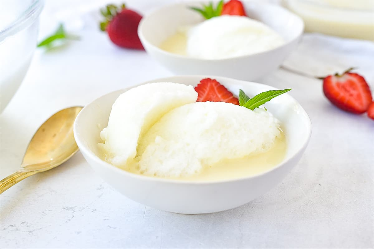 a bowl of snow pudding with a strawberry on it