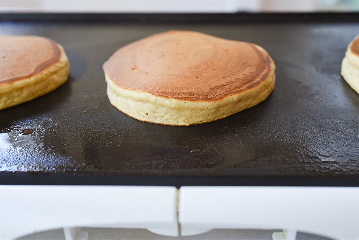 pancakes cooking on griddle