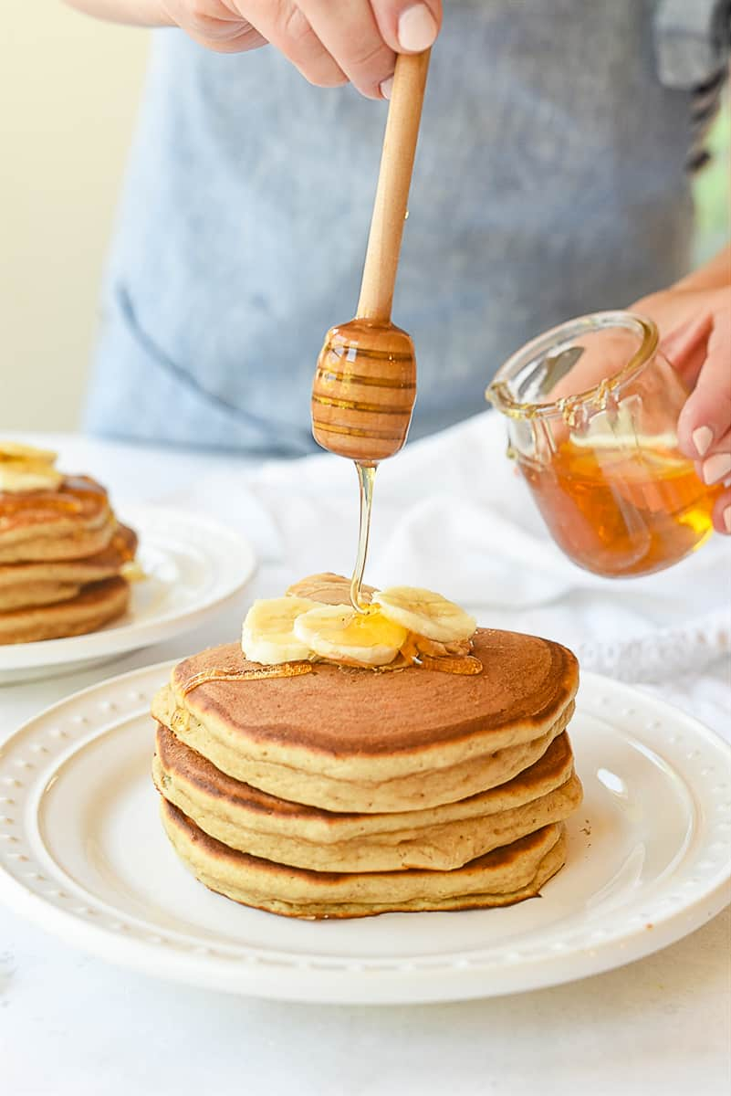 pouring honey on pancakes