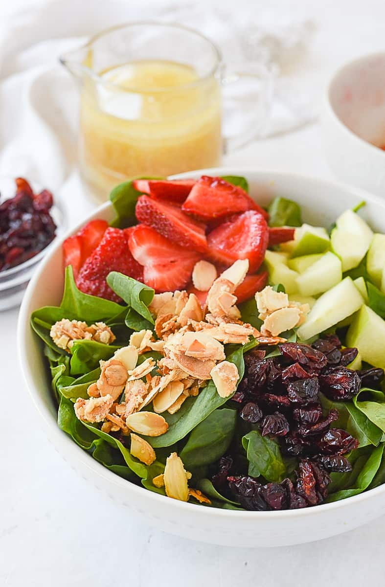 spinach fruit salad ingredients in a bowl