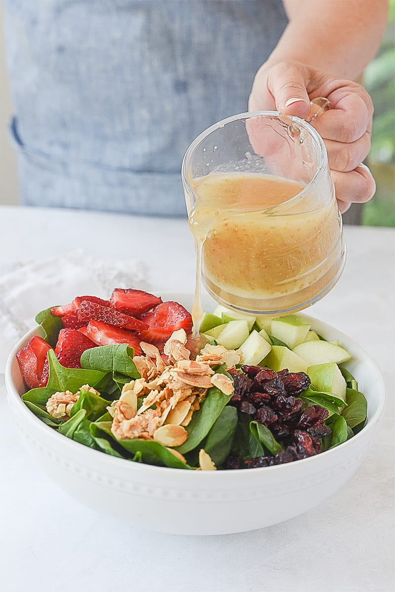 pouring dressing over spinach fruit salad