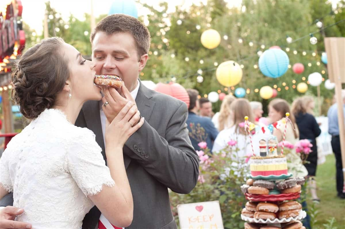 bride and groom eating a donut