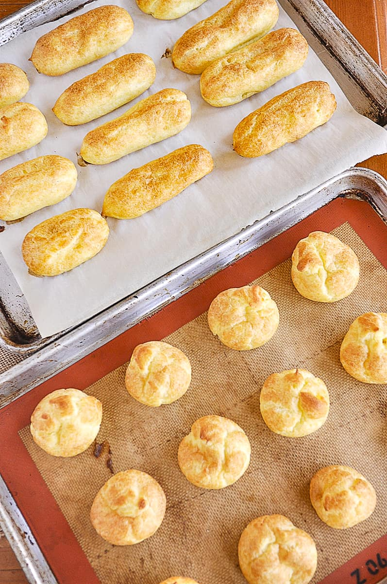 eclairs and cream puffs on a baking sheet