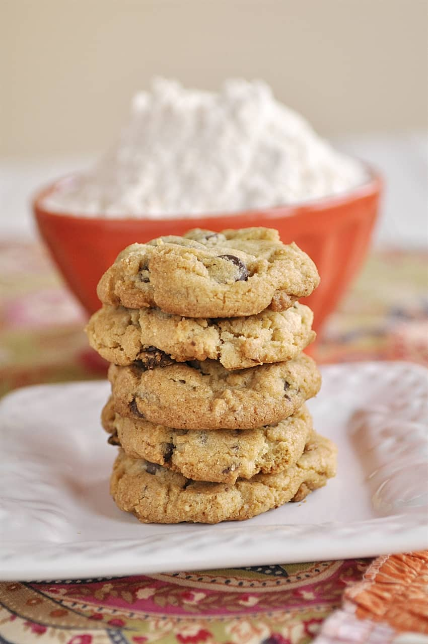 stack of cookies with a bowl of flour