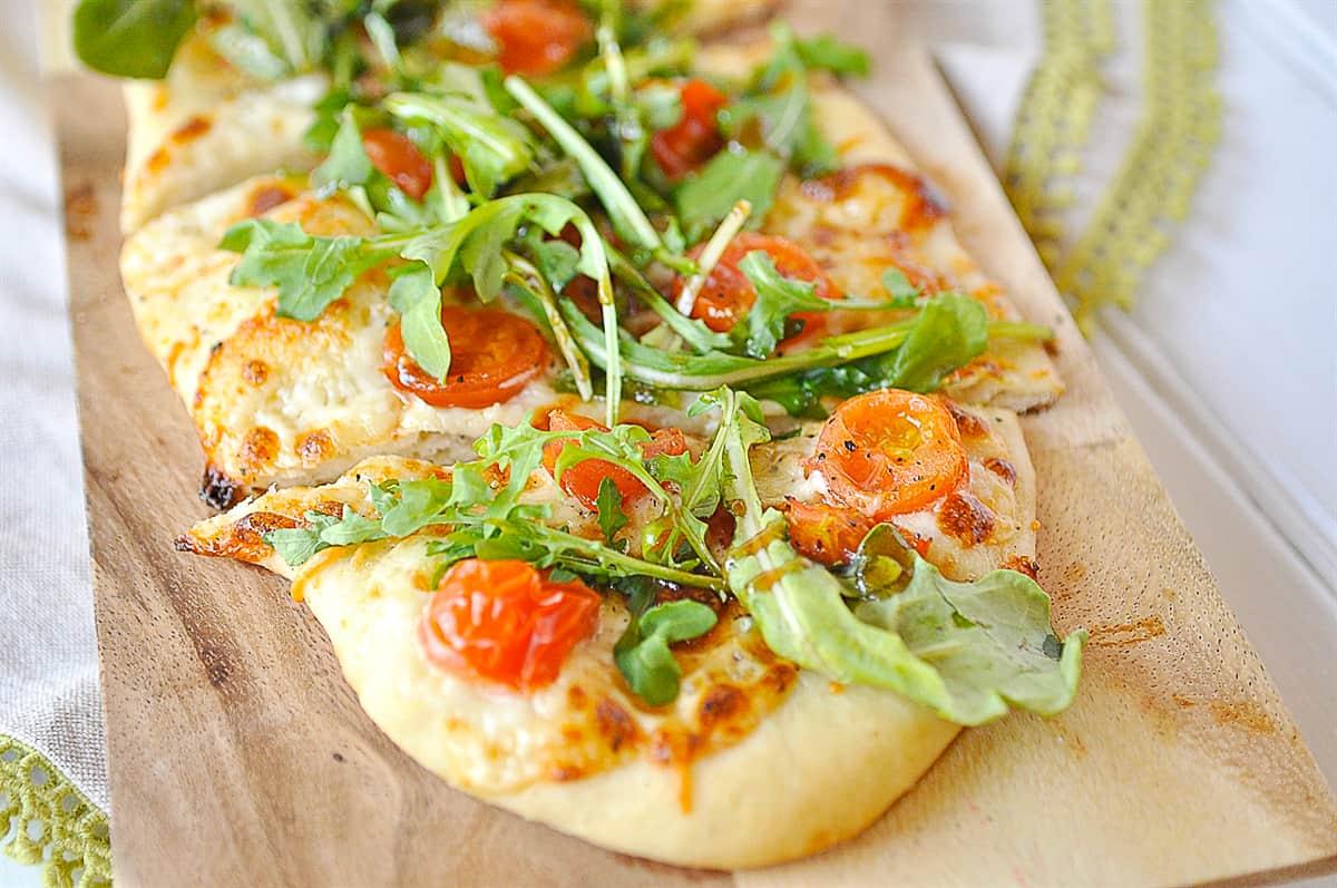 close up of arugula salad pizza