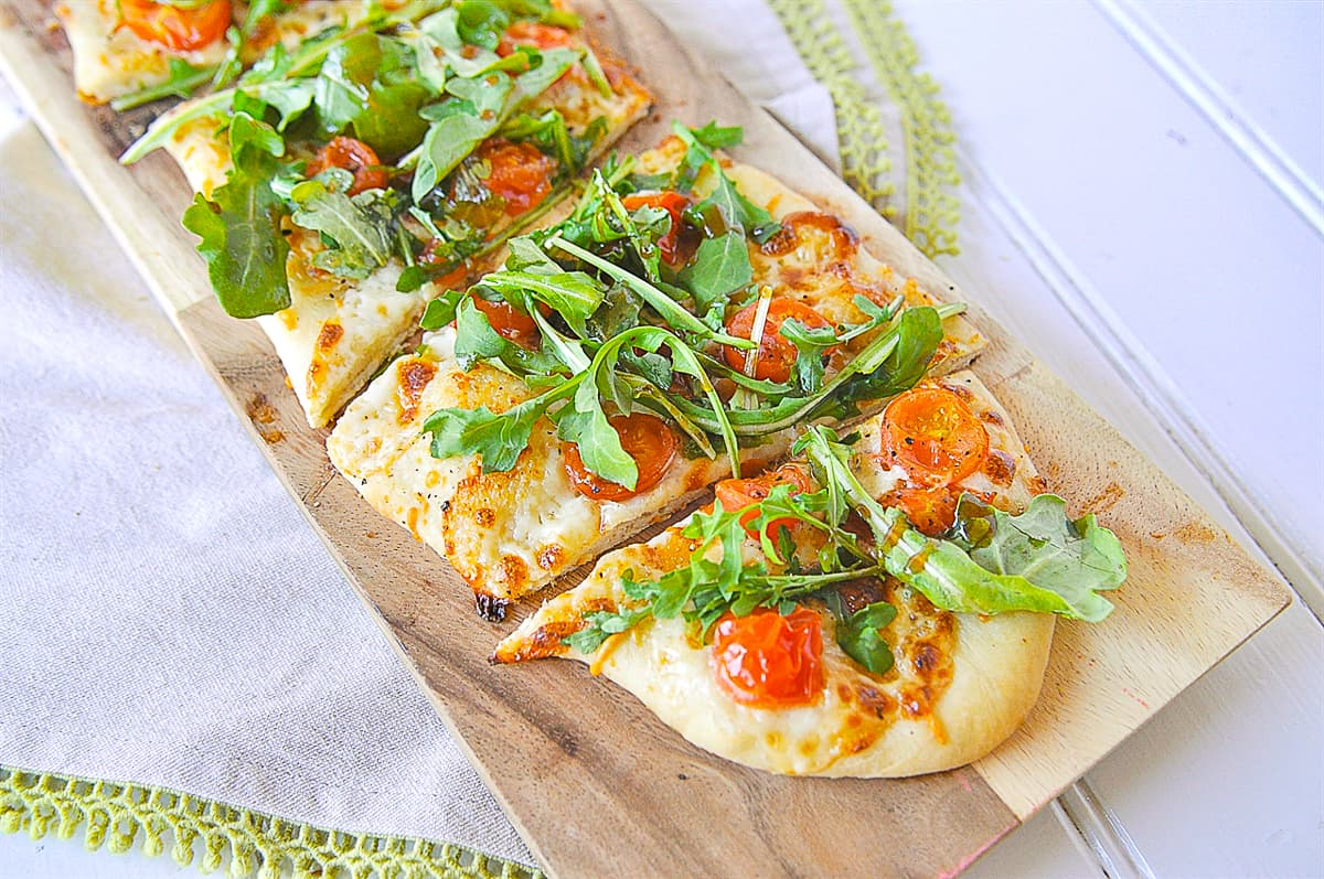 flat bread pizza with arugula salad on it