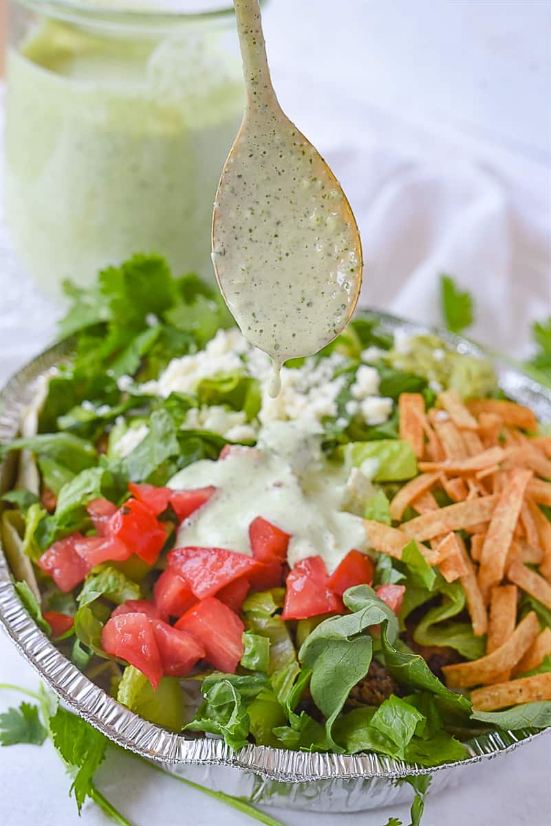 drizzling dressing over salad