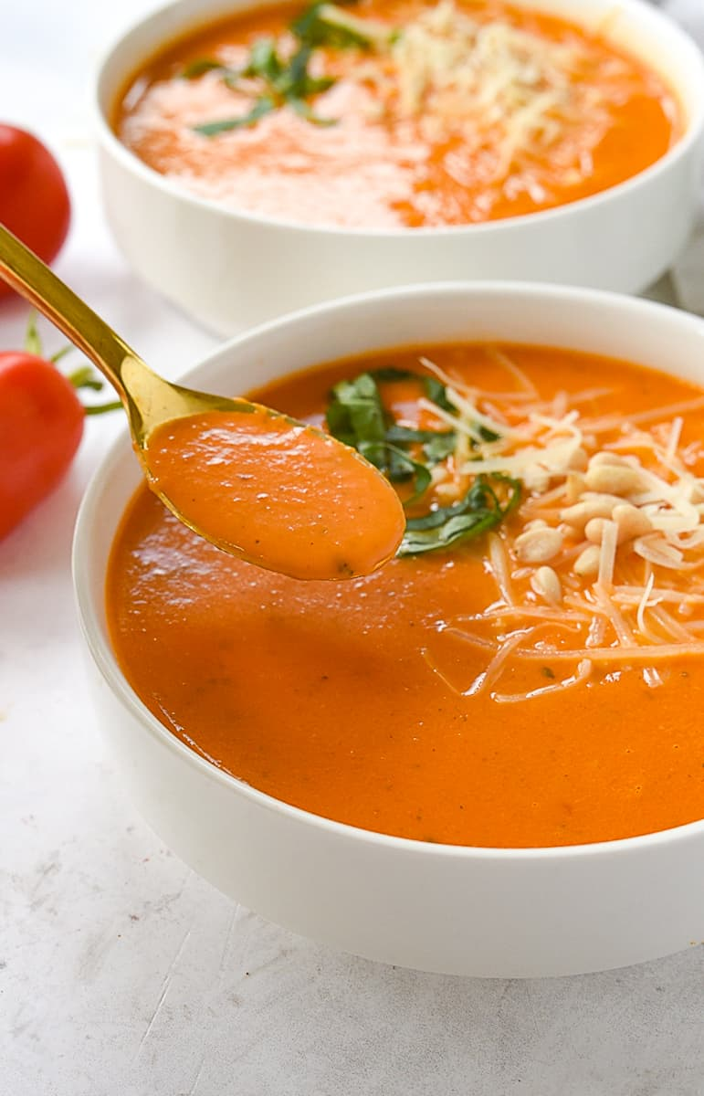 spoonful of tomato soup and bowl