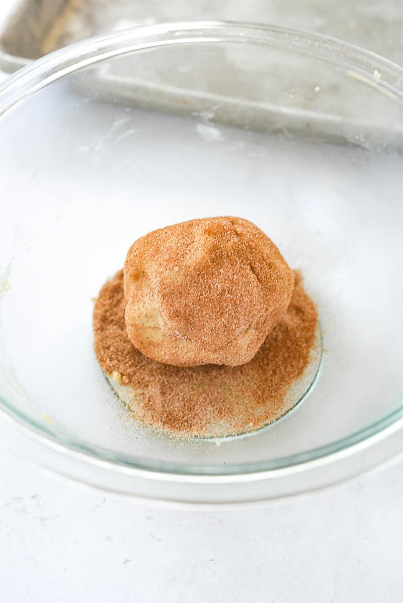 rolling dough into cinnamon sugar
