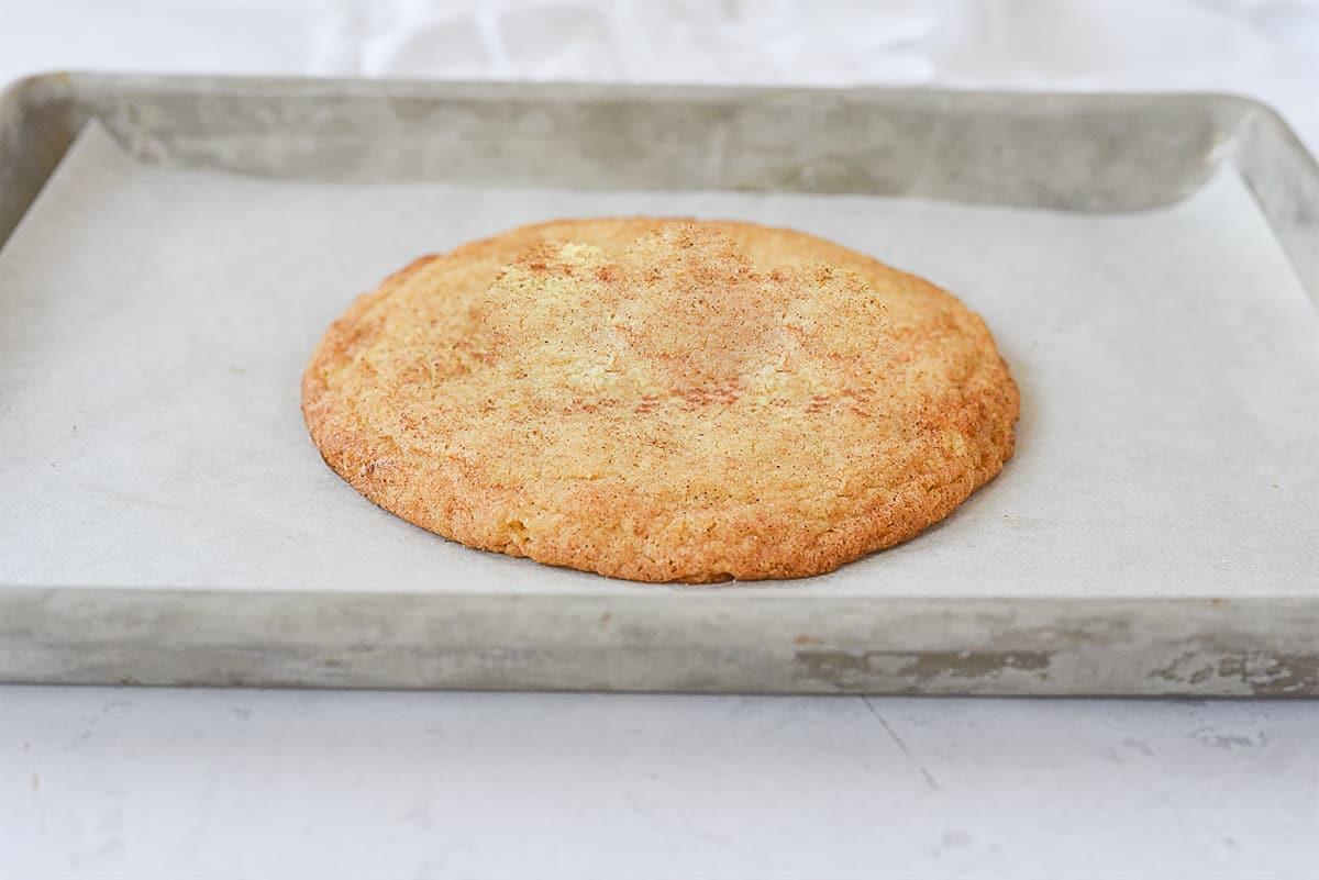 big snickerdoodle cookie on baking sheet