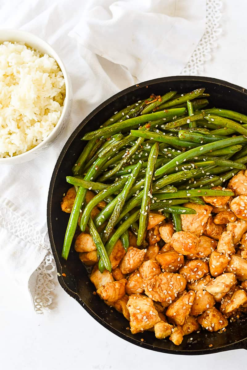 stir fry chicken and beans with a bowl of rice