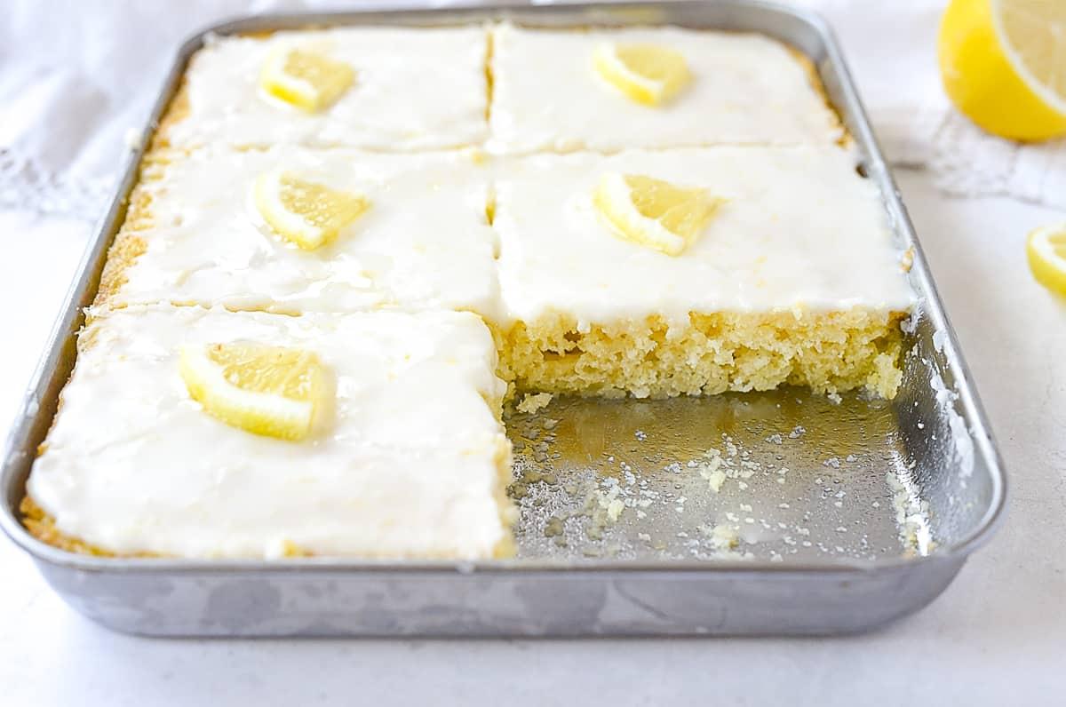 lemon sheet cake with a piece missing