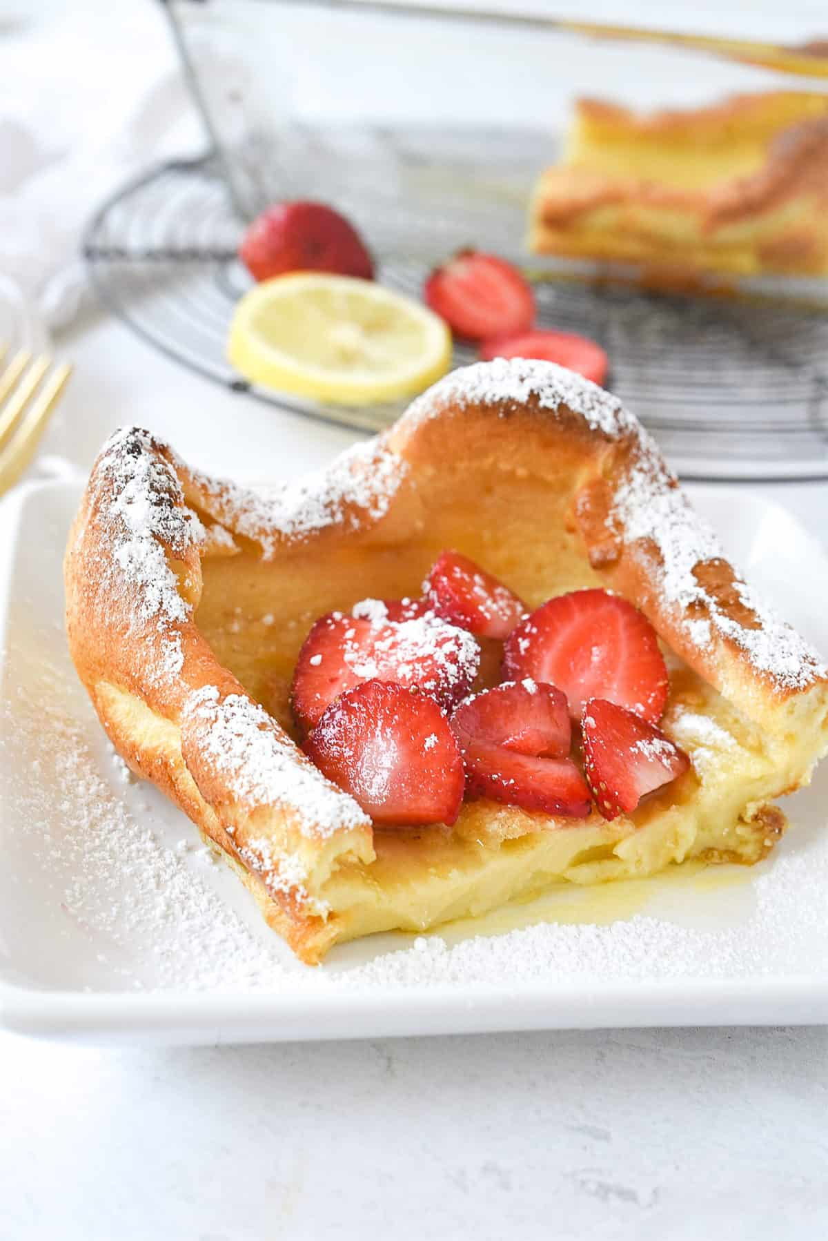slice of dutch baby pancake with strawberries on top