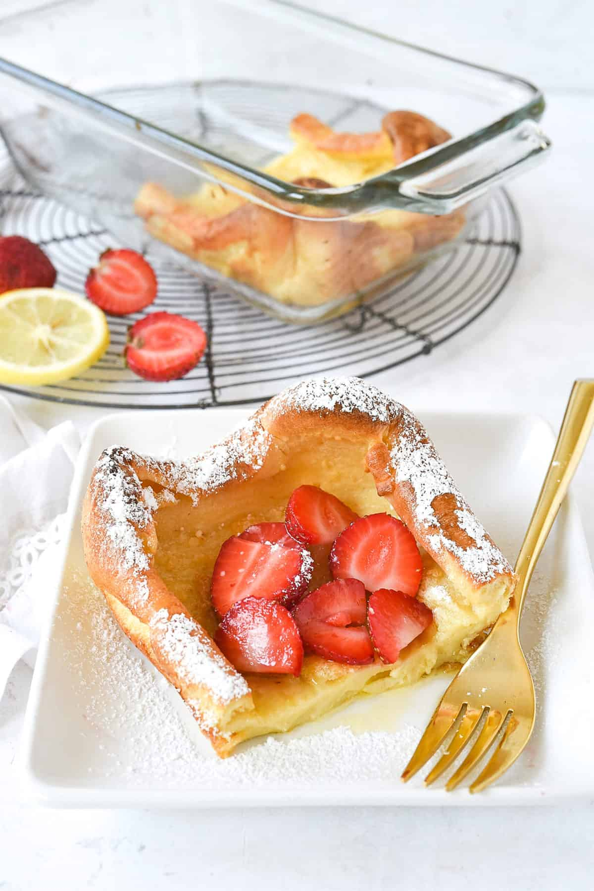 slice of dutch baby with strawberries  on top