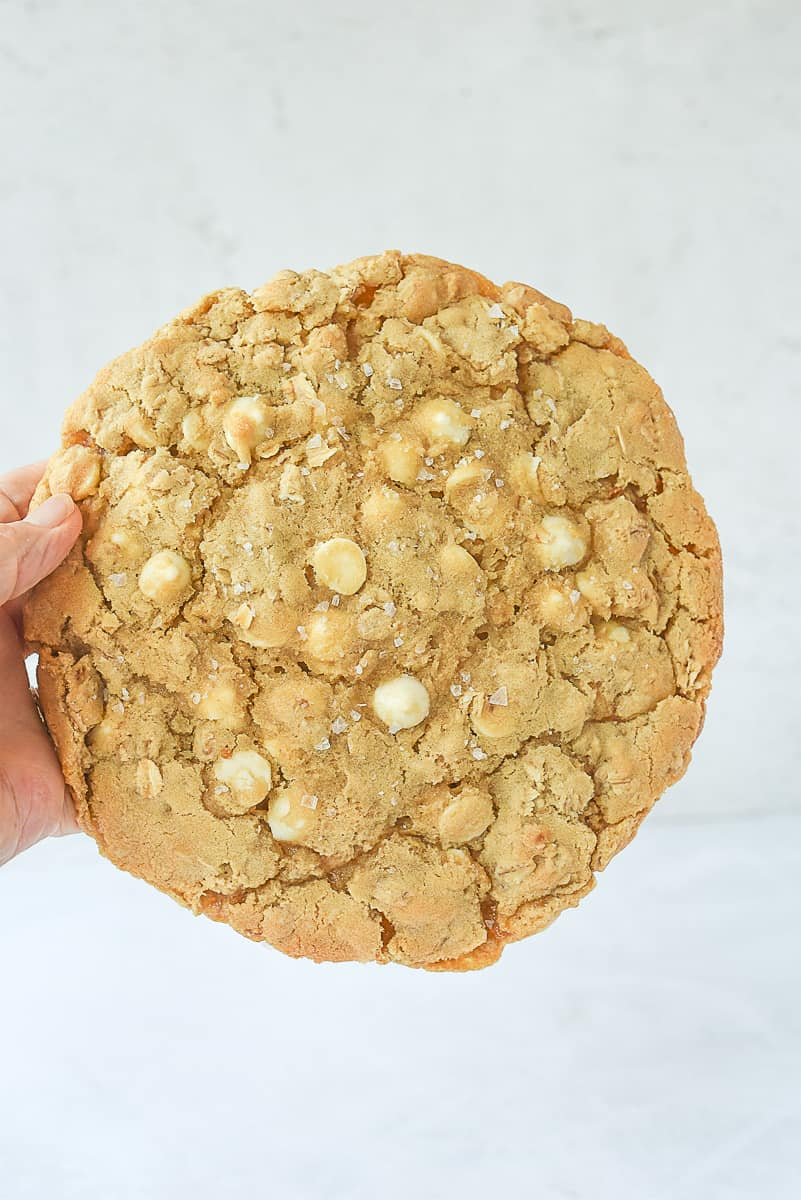 hand holding a salted white chocolate chip oatmeal cookie
