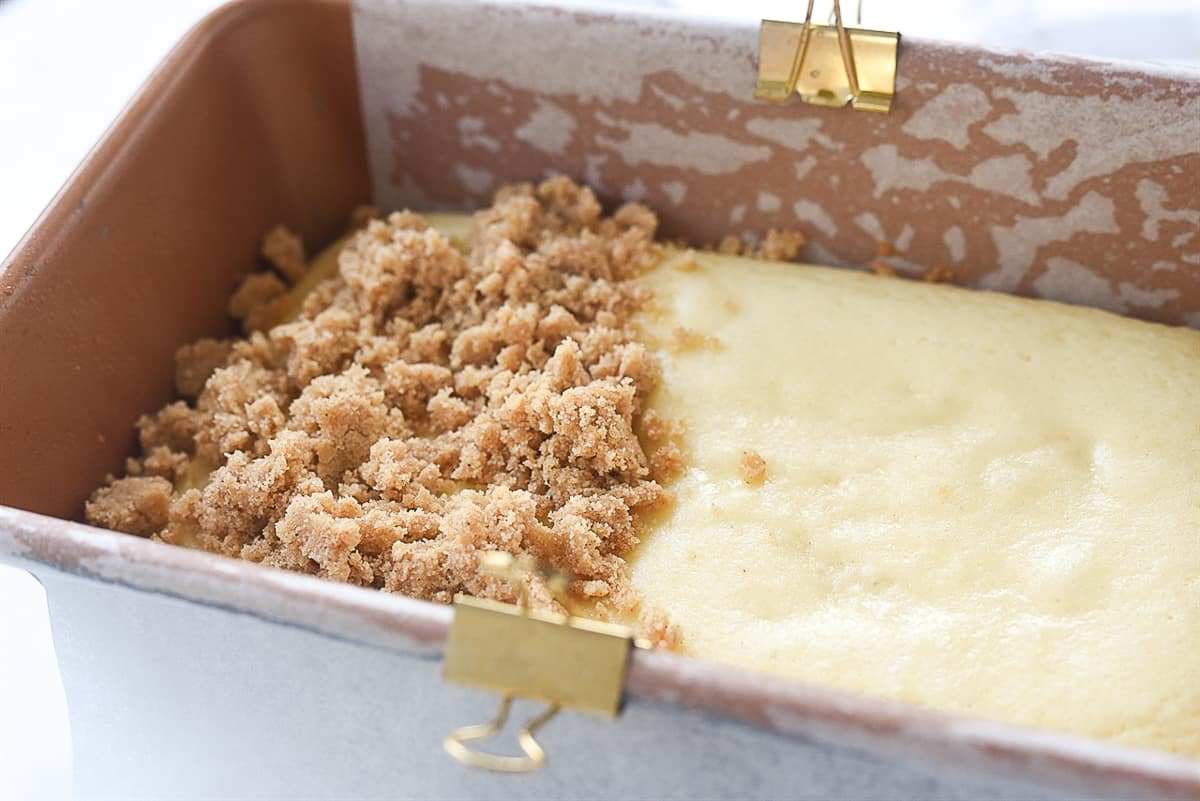 putting streusel topping on coffee cake
