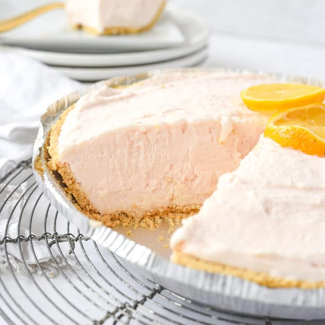pink lemonade pie on a rack with a piece mkissing