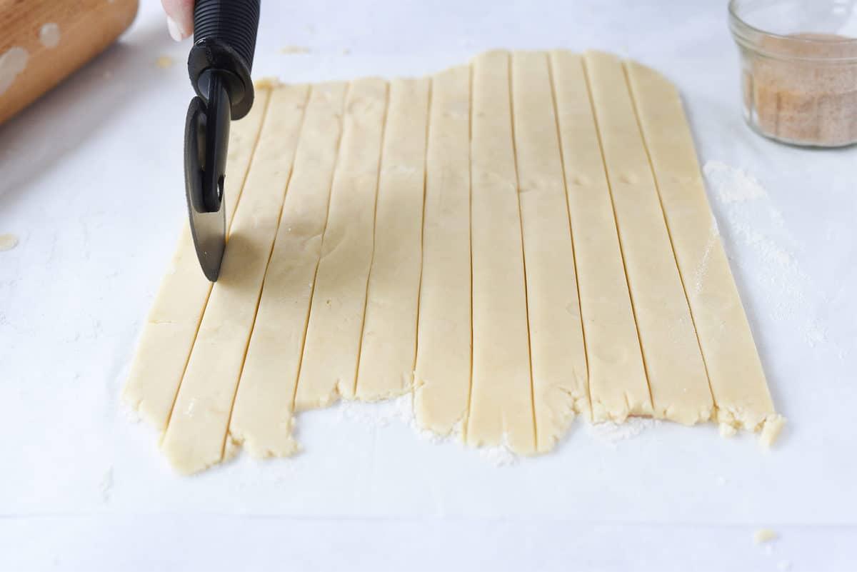cutting dough with pizza cutter