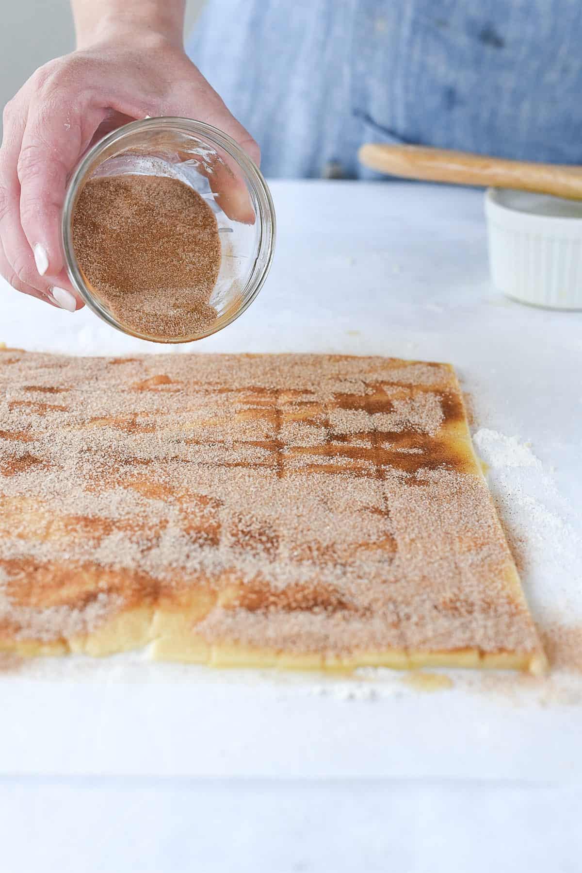 sprinkling pie dough with cinnamon sugar